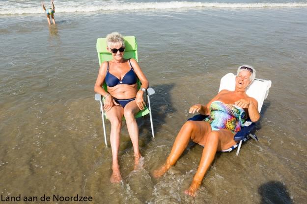 Nederland, The Netherlands, Hoek van Holland 15-09-2016 Drukte op het strand tijdens de ongewoon hete septemberdagen. Veel mensen zoeken verkoeling aan de kust. Een ouder echtpaar in hun ligstoel. De man leest een krant. Foto: Bert Spiertz